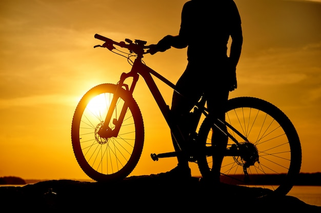 Горный байкер силуэт в восходе солнца