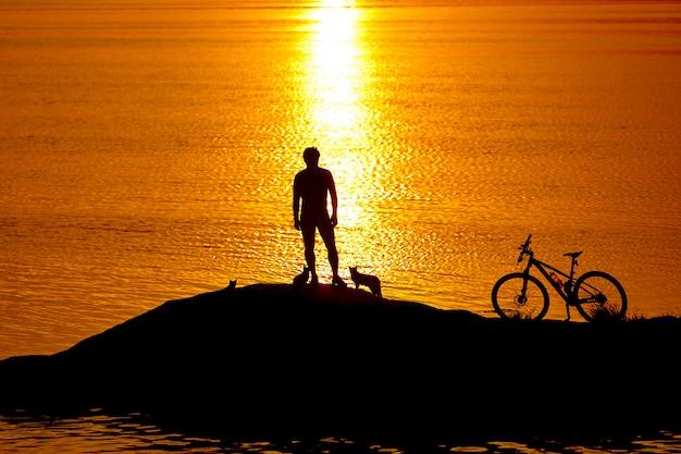 Спортивный парень на велосипеде возле реки вечером