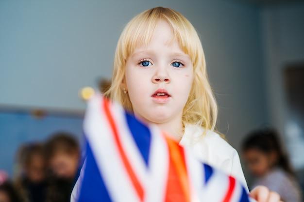 小さな女の子が英国の旗で遊ぶ