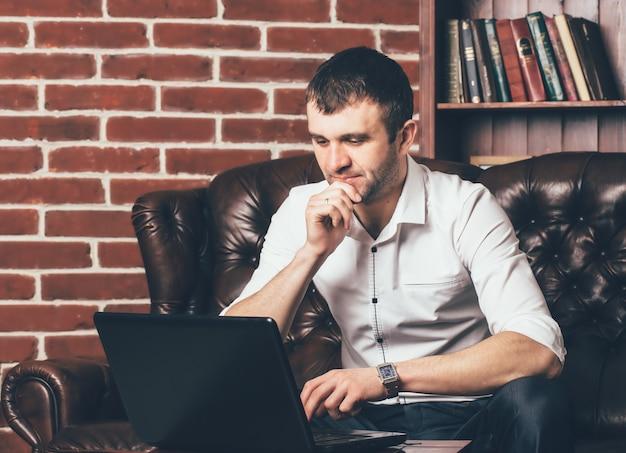 ビジネスマンはオフィスでラップトップに取り組んでいます。彼はテーブルに座る。レンガの形で装飾的な壁