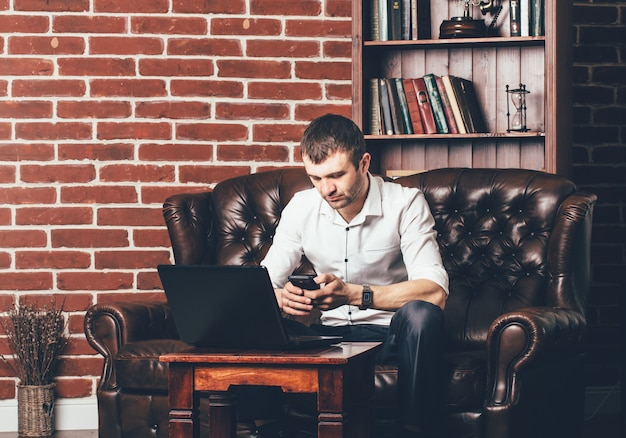 忙しい人は電話番号を呼び出します。ビジネスマンは彼のラップトップの後ろに彼のキャビネットにいます。