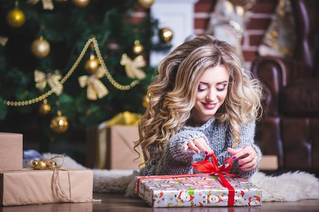 Портрет счастливой молодой рождественской женщины пытается угадать, что находится в подарочной коробке возле елки