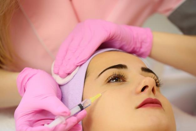 医療ソファのバスローブで横になっている目のゾーンでボトックス注射を受ける女性