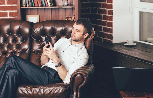 男は快適な革のソファに座っていて、彼の手に電話を持っています。ビジネスマンはラップトップの後ろの仕事から休んでいます。