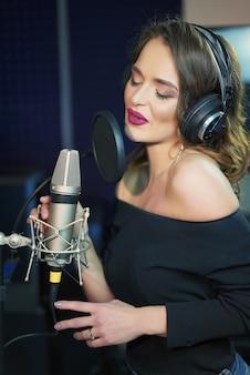 Портрет молодой женщины, запись песни в профессиональной студии.