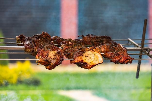 串にひっくり返したシシカバブが火の上にぶら下がっています。このおいしい食べ物は食欲をそそるように見えます