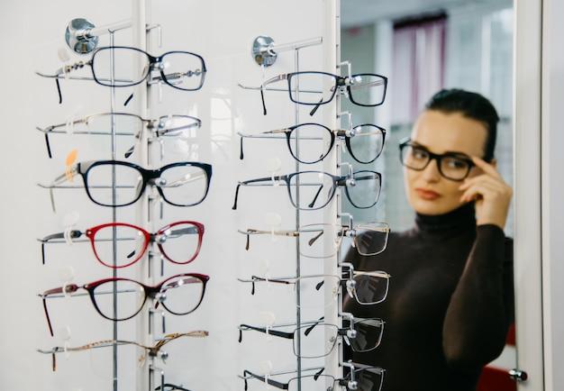 Стенд с очками в магазине оптики с красивой девушкой