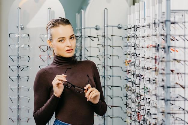 眼鏡屋で眼鏡をかけている美しい少女。