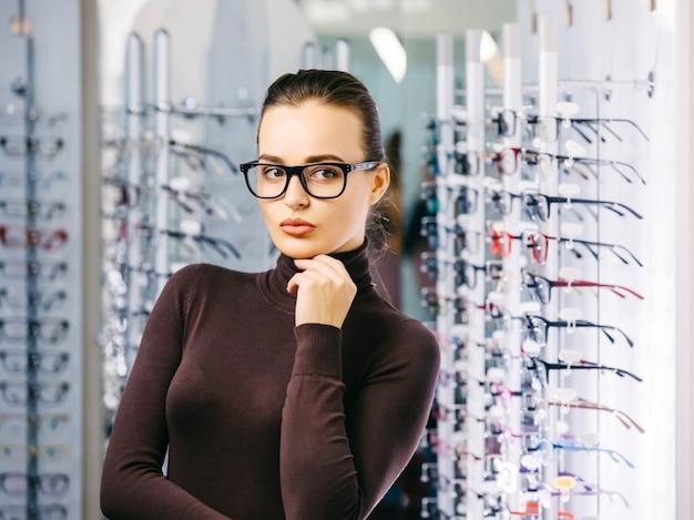 Молодая красивая девушка в очках возле стенда в магазине оптики.