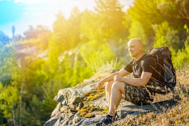 彼の肩にバックパックを持つ旅行者は岩の上に座っています