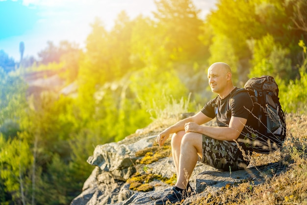 Путешественник с рюкзаком на плечах сидит на скале