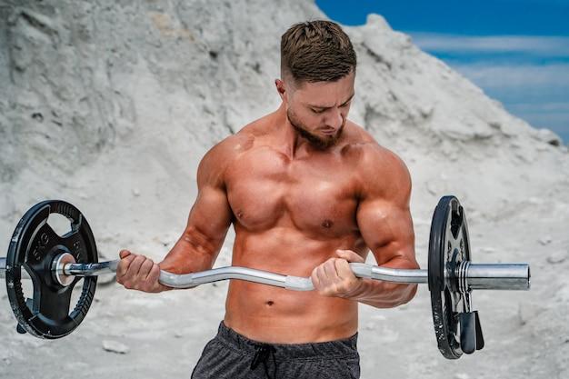 屋外のバーベルで演習を行う筋肉のセクシーな男。ボディービルとアウトドアスポーツ