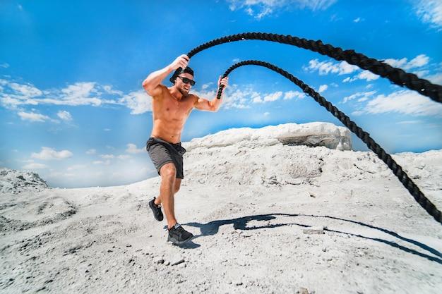 バトルロープでワークアウトする筋肉の男。屋外の戦いロープでワークアウト運動の若い男。スポーツフィット運動。