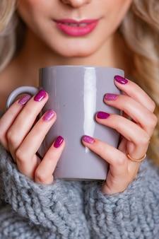 灰色のマグカップを持つ女性の手