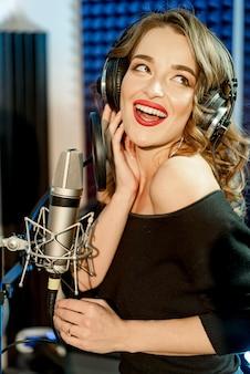 マイクの前でヘッドフォンで魅力的な女の子の歌手は口を大きく開けて、彼女の顔に幸せの表情で歌います。レコーディングスタジオで歌っている若い女性。
