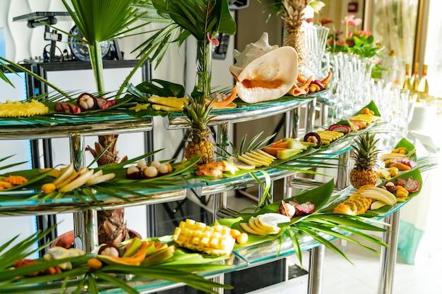 Ярко оформленный шведский стол с различными экзотическими фруктами для гостей на свежем воздухе. ассорти деликатесов из экзотических фруктов, ресторанная еда на мероприятии.
