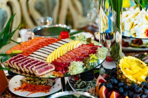 お祝いテーブルのプレートにレモンでスライスした肉の種類。肉とレモンの特別な皿の上に素敵に装飾された皿。閉じる