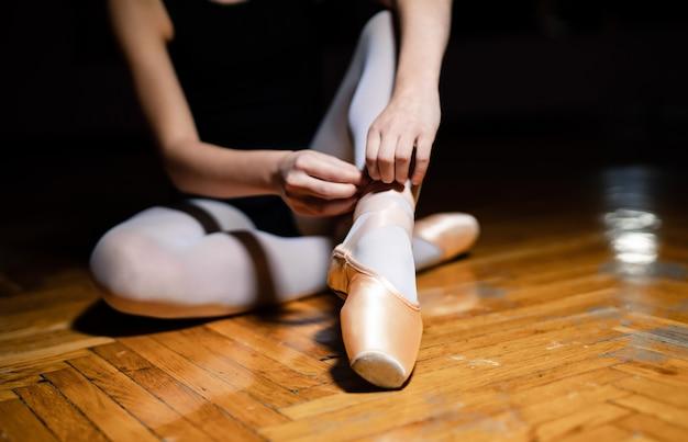 未知のバレリーナは、バレエのクラスで木製の床にトウシューズのリボンを結び付けています。バレリーナは細い足のポアントを結びます。閉じる