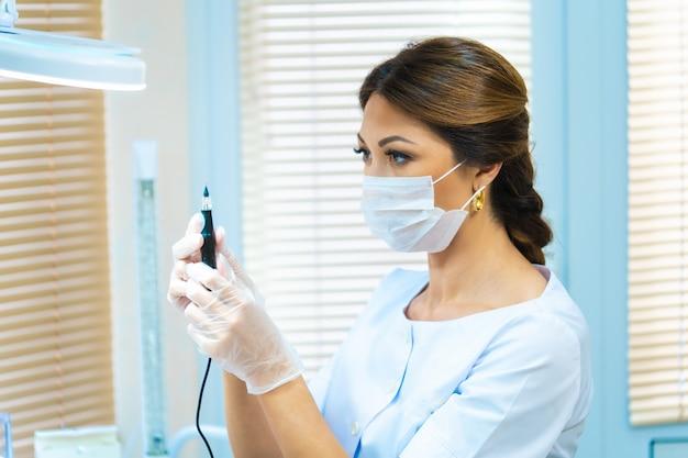 素敵な若い女性の美容師は、明るいオフィスに立って、眉タトゥーの特別なデバイスを調べます。美容師は、眉毛の恒久的なメイクアップのために器具をチェックします。