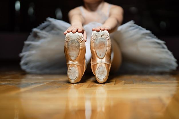 教室の床に座って、木製の床に白いバレエシューズのつま先を保持しているバレリーナ。小さな女の子のクラシックバレリーナのポイント。閉じる