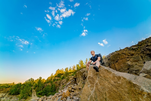 バックパックを持った旅行者は、鋭い端を持つ大きな石の上に座る