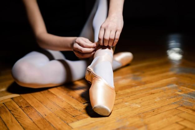 木製の床に座って、トレーニングの前にバレエシューズを結ぶバレエダンサー。バレリーナは彼女の拍を縛ります。閉じる