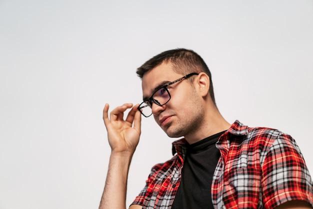 眼鏡のハンサムな男。彼の眼鏡に触れるスマートな男