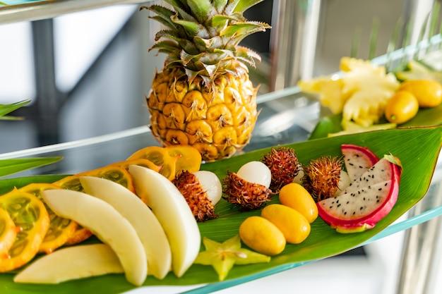 多くのエキゾチックな新鮮な果物を宴会用のガラステーブルに混ぜて