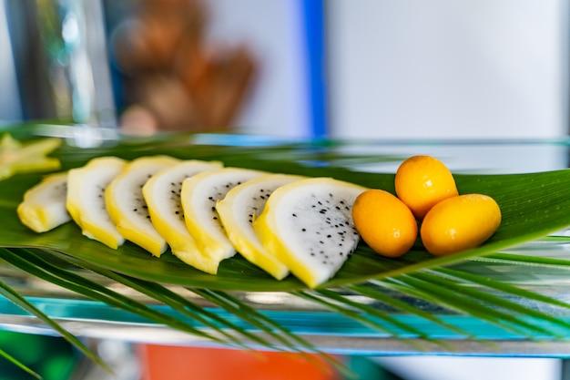 Свежие экзотические фрукты красиво украшены для гостей на большом зеленом листе.