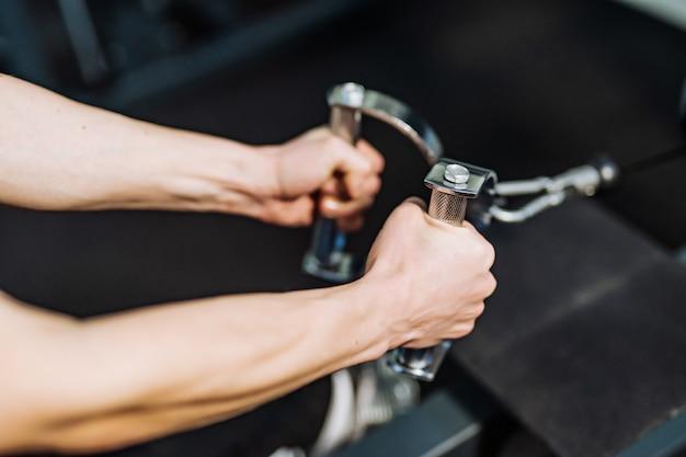 ジムのシミュレーターの金属製ハンドルを保持している強いスポーツウーマンの手。