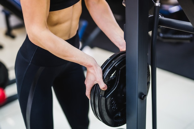 Сильное тело женщины фитнеса принимая плиты штанги в спортзале.