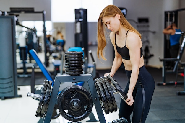 Красивая сильная молодая женщина спорт кладет диск штанги на спортзал фитнеса.
