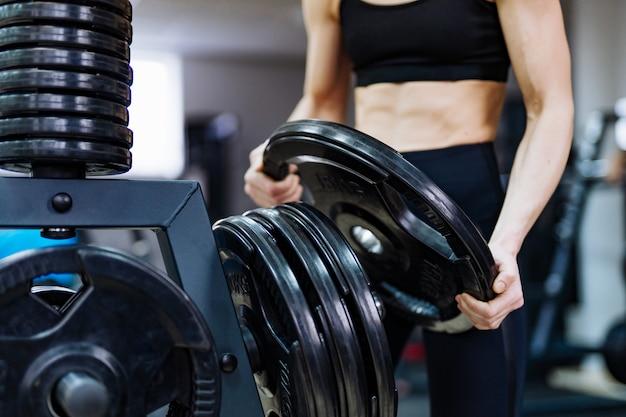 Руки сильной женщины держа диск от штанги и кладя его к железным дискам в спортзал.