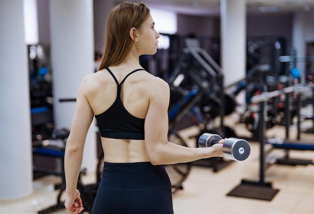 モダンなジムでダンベルを持つスポーティな女性の背面図。