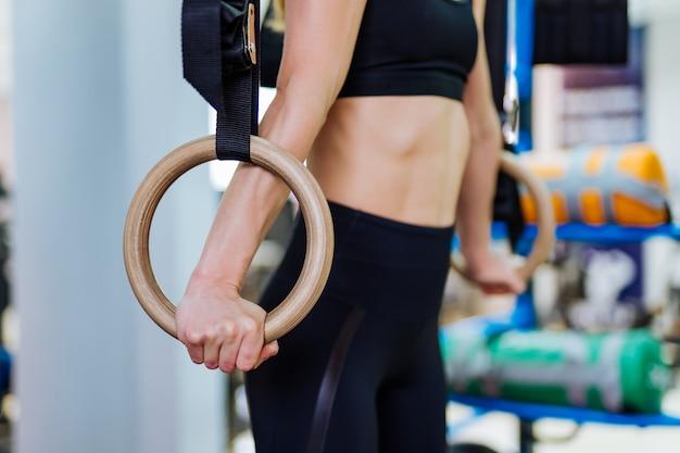 体操リングのペアを保持している女性の体のショットをトリミングしました。