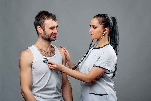Красивая молодая женщина шутит с красивым молодым мужчиной, проверка сердцебиения с помощью стетоскопа