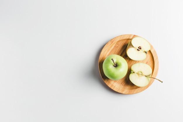 白いテーブルの上の緑のリンゴ