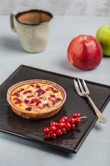 赤スグリの実と明るい背景にコーヒーのカップとアップルパイ