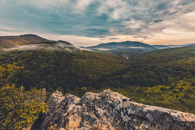 雲が浮かぶ渓谷の上の山の秋の寒い朝の夜明け