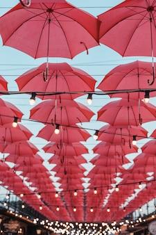 赤い傘と電球が通りの屋根のようにぶら下がっています