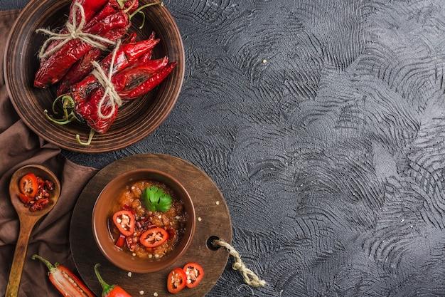 Пряный перец чили на темном фоне в керамических тарелках