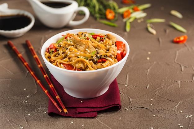 Лапша удон с курицей и овощами в тарелке с красными палочками и соевым соусом.