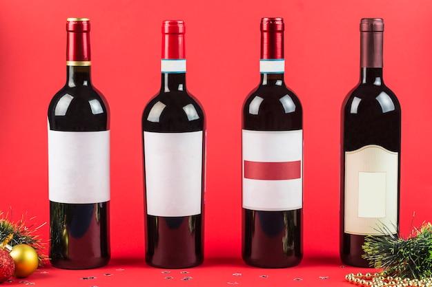 暗いブルゴーニュの背景のクローズアップに赤と白ワインのボトル。新年とクリスマス。