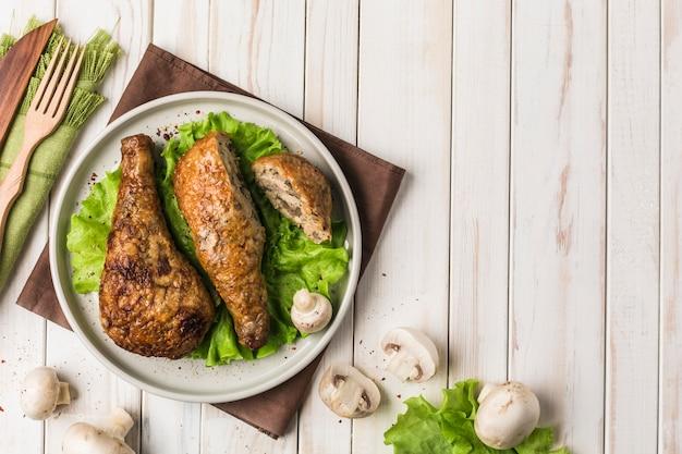 Жареная куриная голень, фаршированная грибами, плоская тарелка с листьями салата на светлое дерево.