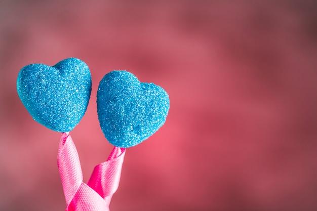 Мармелад в сахарно-синем цвете в виде сердечек на палочках с бантиком на светло-розовом фоне