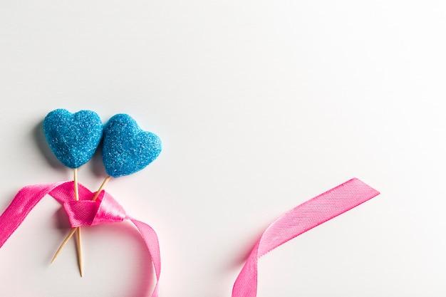 Мармелад в сини сахара в форме сердец на ручках с лентой на белом крупном плане предпосылки с космосом экземпляра. день святого валентина