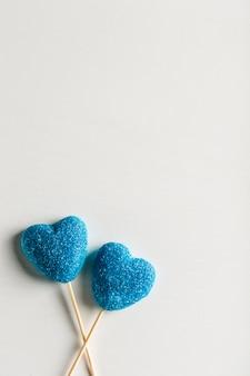 Мармелад в сахарно-голубой форме сердца на палочках на белом фоне