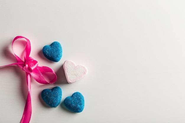 Мармелад в сахарно-голубом и зефир в форме сердца с бантом на белом фоне