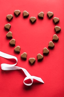 Конфеты в форме сердца на красном фоне для дня святого валентина