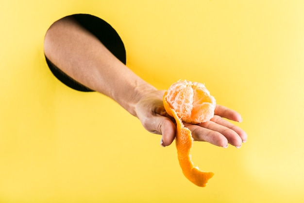 黄色い紙の壁のブラックホールから半分皮をむいたみかんを持っている女性の手。